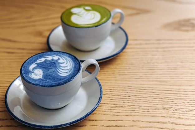 아침 식사는 두 사람입니다. 우유와 커피 한 잔에 맞는 간식. 파란색과 녹색의 두 컵은 하트 패턴과 일치합니다. 블로그 템플릿