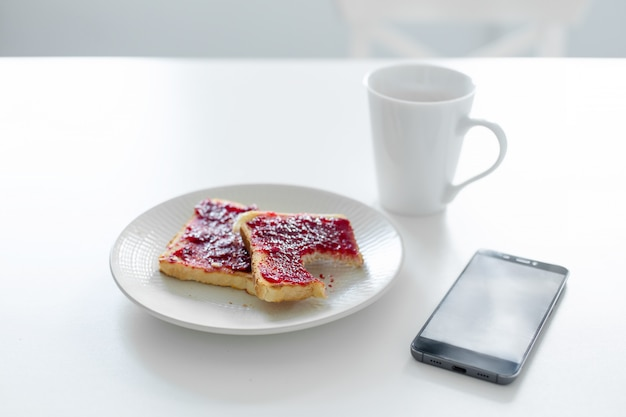 Breakfast is on the table. a cup of coffee and toast with cherry jam next to the phone