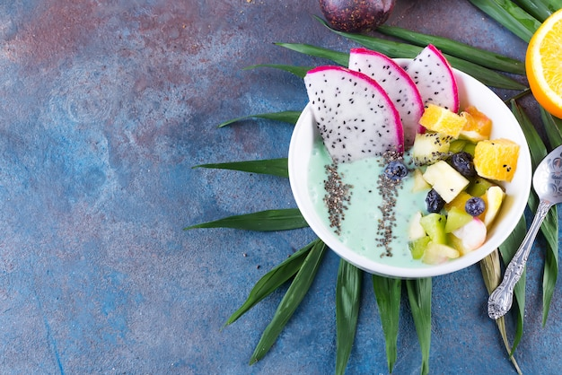 Breakfast kiwi smoothie bowl topped with pitaya, pineapple, chia seeds and berries with palm leaf on stone background, top view