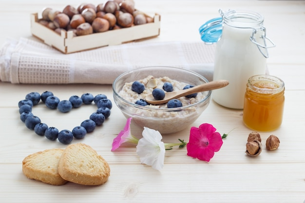 Breakfast of love from oatmeal blueberries with hearts, honey, nuts and milk.