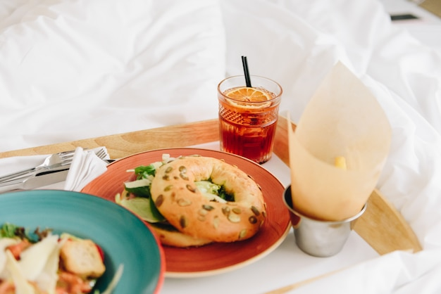 Breakfast or lunch in bed of a panzanella salad with croutons and a bagel with fresh lettuce, two drinks and french fries