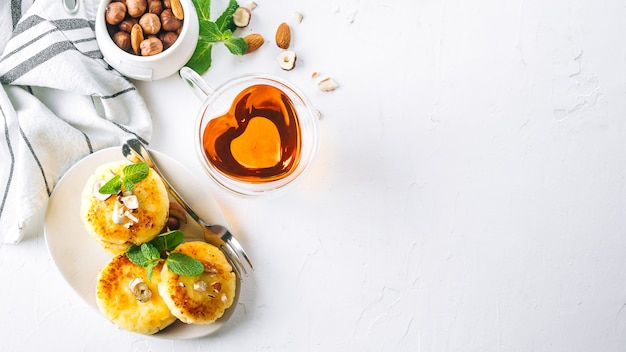 Breakfast or lunch concept. cottage cheese pancakes with honey, nuts and mint. banner image