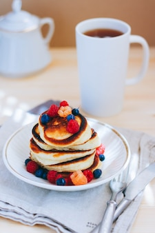 Breakfast, lush pancakes with fresh berries, raspberries and blueberries and a cup of tea