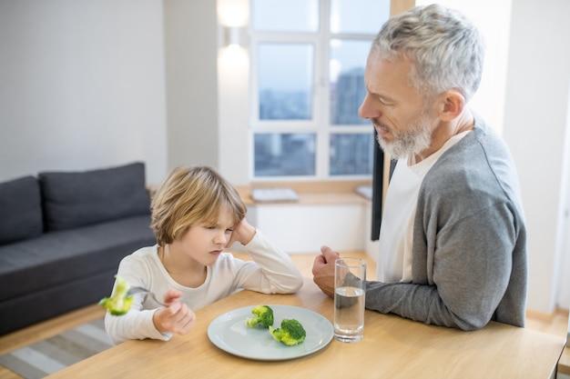 朝ごはん。男の子が不幸に見える間、彼の息子を健康的に食べさせようとしている成熟した男