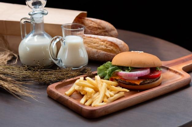 朝食メニュー。木製のテーブルにクラフトビーフハンバーガー、牛乳、フライドポテト。
