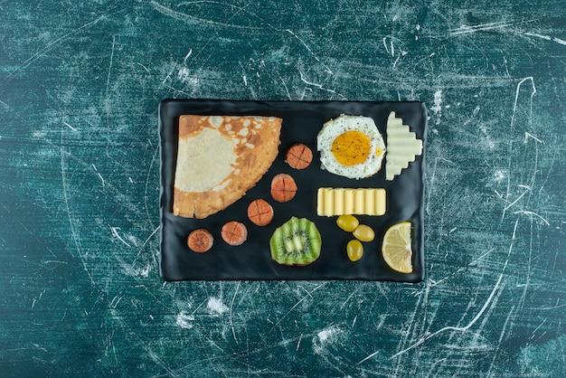 계란, 크레페, 사이드 음식이 있는 나무 판자에 있는 아침 식사 메뉴. 고품질 사진
