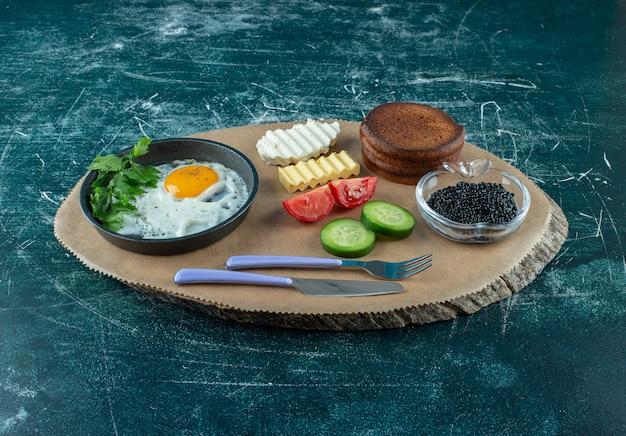 계란 후라이, 캐비어, 팬케이크를 곁들인 나무 판자에 아침 식사 메뉴. 고품질 사진