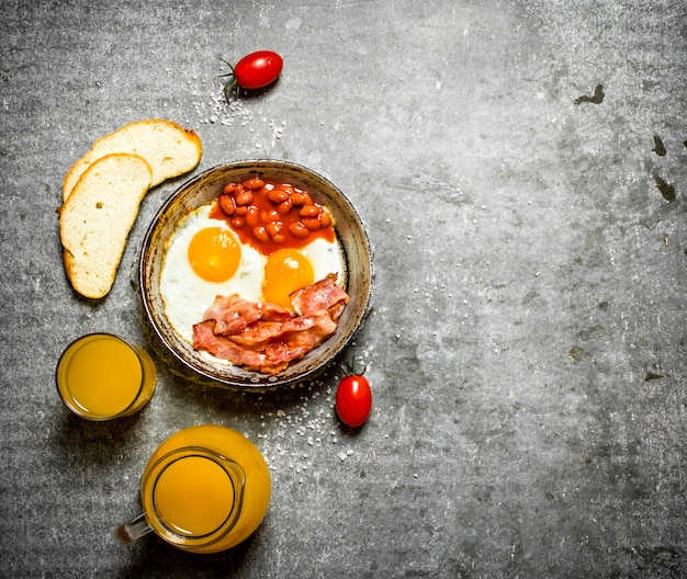 Breakfast in the morning. bacon, fried eggs with beans and orange juice. on the stone table.