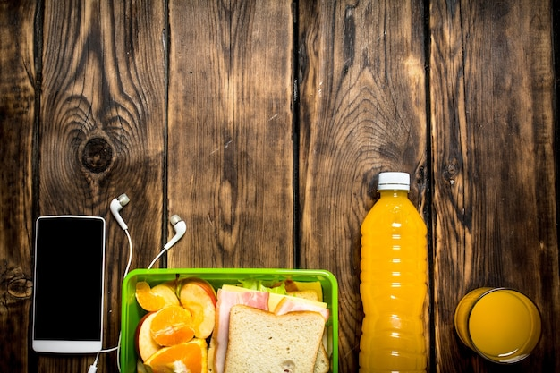 Breakfast in the morning. sandwiches with orange juice and fruit.