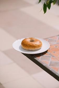 朝食の朝テーブルの背景に白いプレートにドーナツと晴れた暖かい天気。機嫌が良い横から見た