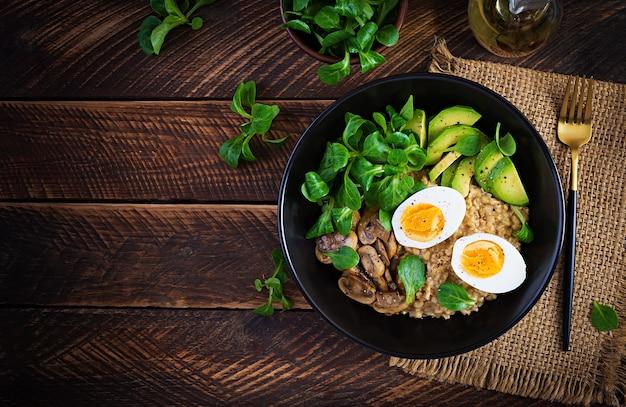На завтрак овсяная каша с вареным яйцом, авокадо и жареными грибами.