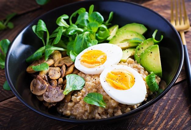 Breakfast oatmeal porridge with boiled egg, avocado and fried mushrooms
