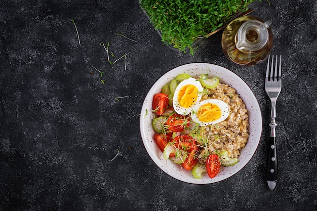 Breakfast oatmeal porridge with boiled egg, cherry tomatoes, celery and microgreens. healthy balanced food. top view, above, copy space