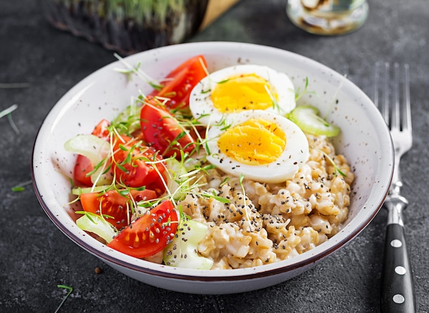 Breakfast oatmeal porridge with boiled egg, cherry tomatoes, celery and microgreens. healthy balanced food.