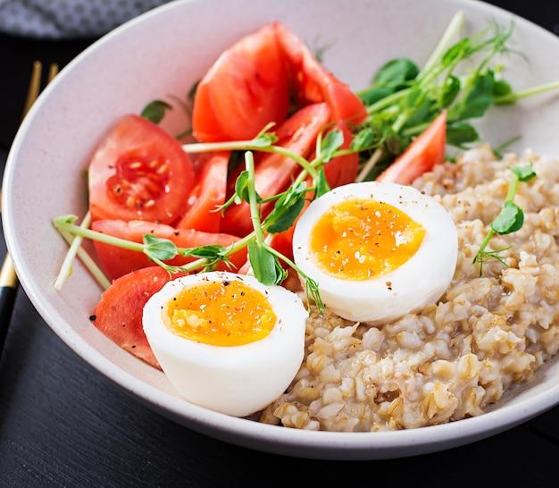 Breakfast oatmeal porridge with boiled egg, cherry tomatoes and microgreens