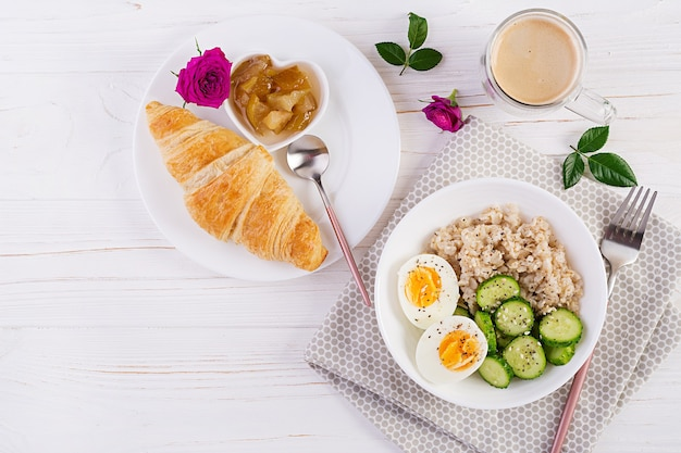 Breakfast oatmeal porridge with boiled egg, cucumber and croissant, jam, coffee. healthy balanced food. top view, flat lay