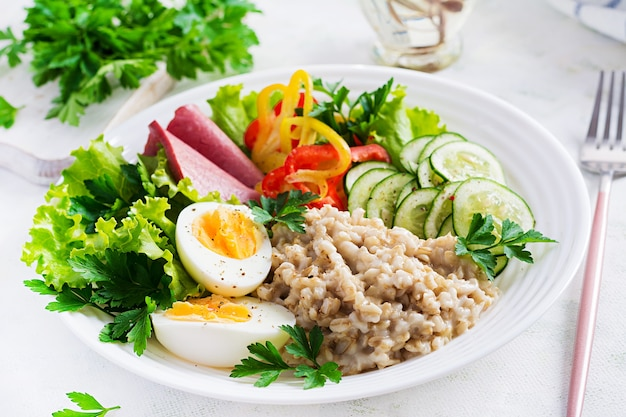 ゆで卵、ハム、野菜のサラダとオートミールのお粥を朝食。健康食品。