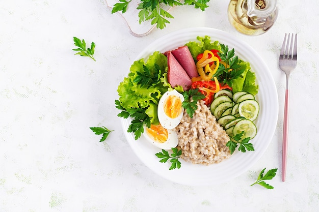 Breakfast oatmeal porridge with boiled egg, ham and vegetables salad. healthy food. top view, overhead,  copy space