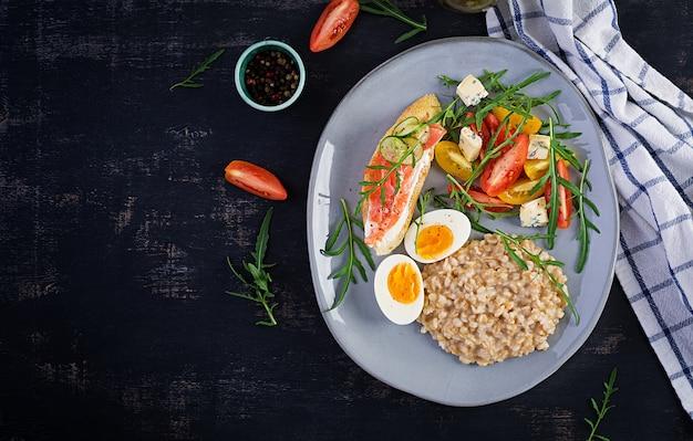 На завтрак овсяная каша с вареным яйцом, бутерброд с лососем и салатом из помидоров. здоровая пища. вид сверху, над головой, копией пространства