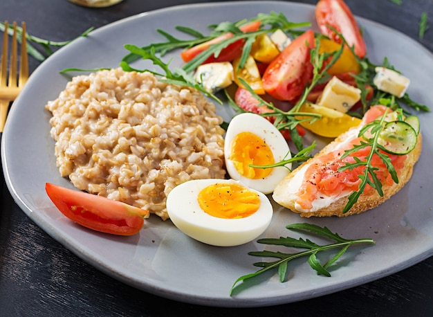 Breakfast oatmeal porridge with boiled egg, salmon sandwich and tomatoes salad. healthy food.