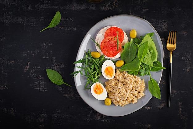 На завтрак овсяная каша с вареным яйцом, бутерброд с помидорами, рукколой и шпинатом. здоровая пища. вид сверху, над головой, копией пространства