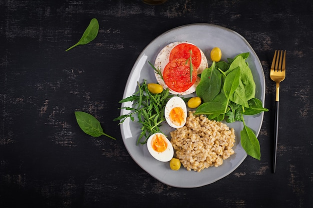 Breakfast oatmeal porridge with boiled egg, tomatoes sandwich, arugula and spinach. healthy food. top view, overhead,  copy space