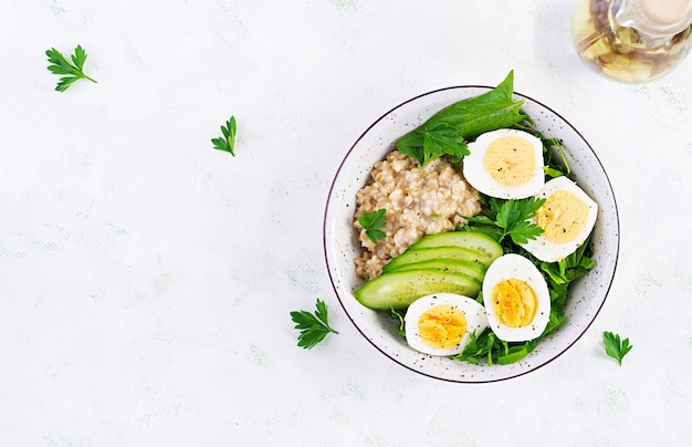 Breakfast oatmeal porridge with boiled eggs, cucumber and green herbs. healthy balanced food. top view, above