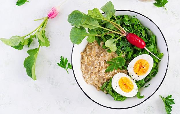 Breakfast oatmeal porridge with boiled eggs, radish and green herbs. healthy balanced food. top view, above
