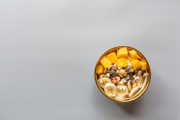 Breakfast oatmeal porridge with fresh fruits, chia seeds and hazelnuts.