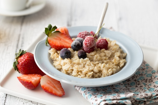 Breakfast oatmeal porridge with fruits berries and coffee cup.
