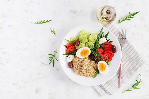 토마토, 오이, 올리브 및 계란의 그리스 샐러드와 함께 아침 오트밀 죽. 건강한 균형 잡힌 음식. 평면도, 평면 위치, 복사 공간