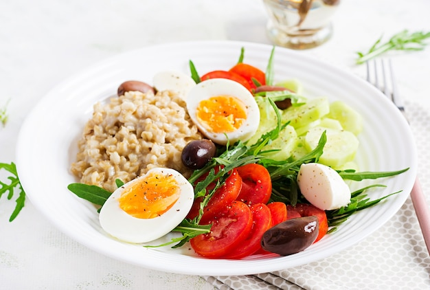 Breakfast oatmeal porridge with greek salad of tomatoes, cucumbers, olives and eggs. healthy balanced food.