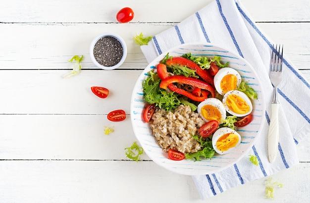 На завтрак овсяная каша с зеленью, вареным яйцом, помидорами и болгарским перцем. здоровое сбалансированное питание. вид сверху, над головой, копией пространства