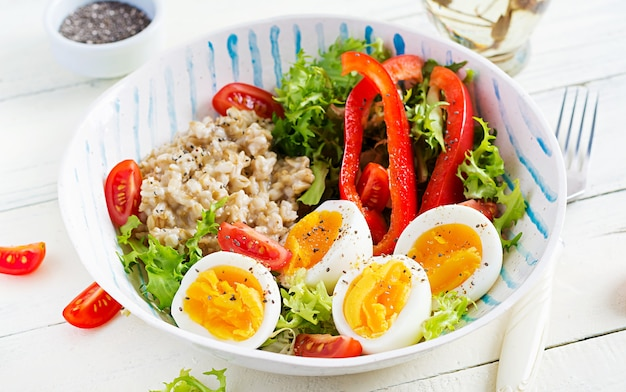 Breakfast oatmeal porridge with green herbs, boiled egg, tomatoes and paprika. healthy balanced food.