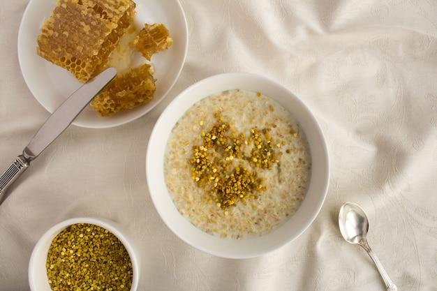 朝食:テキスタイルの背景に白いボウルにビーポーレンと蜂蜜とオートミール。上面図。コピースペース。