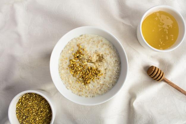 Завтрак: овсяные хлопья с пчелиной пыльцой и медом в белой миске на текстильном фоне. вид сверху. копия пространства.