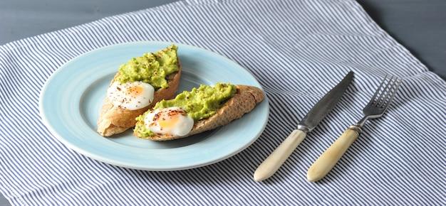 바게트, 계란 및 으깬 아보카도의 아침 식사