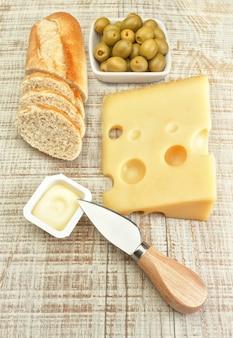オリーブのパンとチーズプレートの朝食。ボードテクスチャ。