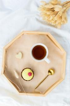 Завтрак из торта с чаем на подносе в постели с букетом цветов