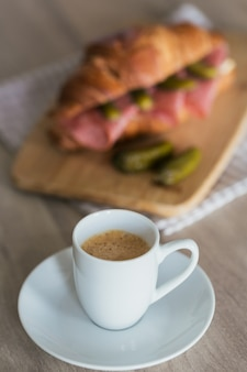 Завтрак из кофе и бутерброда с круассаном, фаршированным салями и корнишоном на кухне