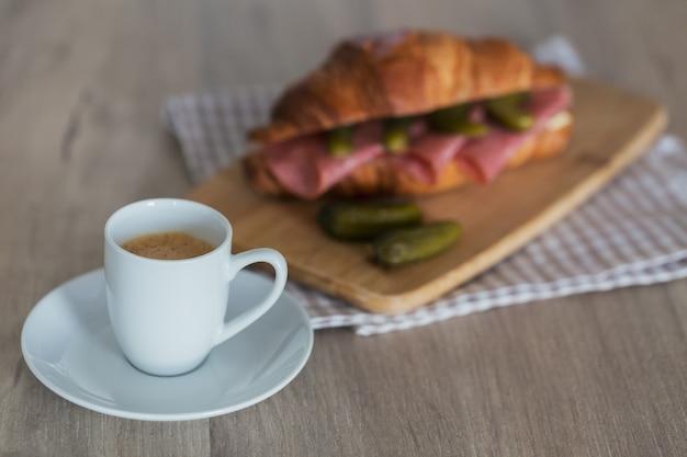Завтрак из кофе и бутерброда с круассаном, фаршированным салями и корнишоном.