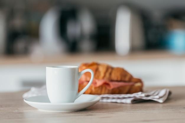 Завтрак из кофе и бутерброда с круассаном, фаршированным салями на кухне