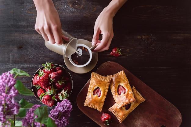 딸기 잼과 신선한 딸기를 곁들인 우유 퍼프와 커피의 아침 식사