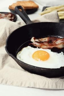 냄비에 계란과 튀긴 베이컨의 아침 식사