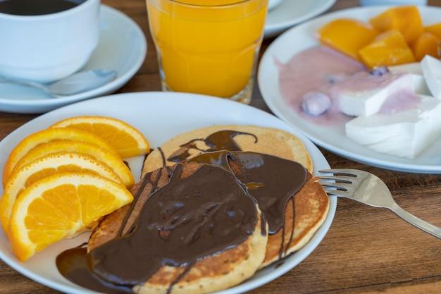 Завтрак из многих блюд и напитков на деревянном столе крупным планом. концепция питания