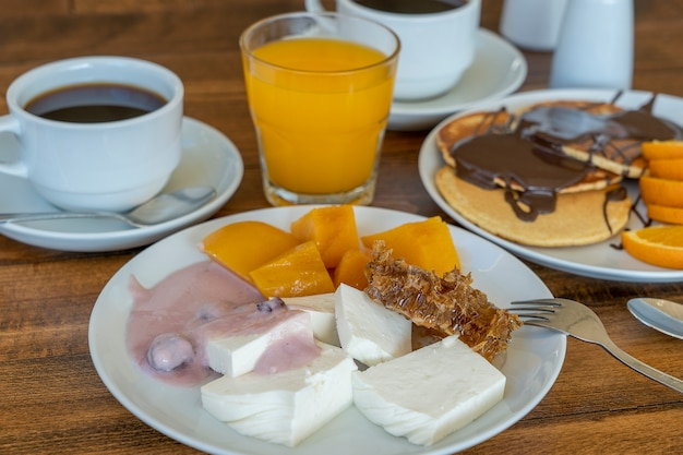 木製のテーブルでたくさんの料理や飲み物の朝食