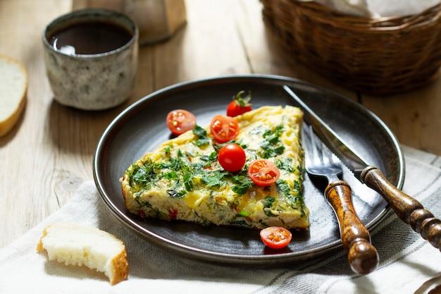野菜、ハーブ、チーズを添えたオムレツの朝食。パンとコーヒーを添えて。