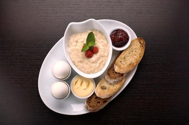 暗い表面でのお粥、バター、ゆで卵、ジャムとトースト、クルトンの朝食