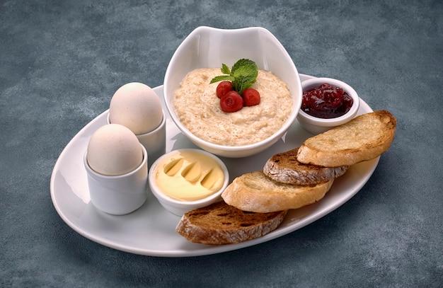 お粥、バター、ゆで卵、ジャムとトースト、クルトンの朝食