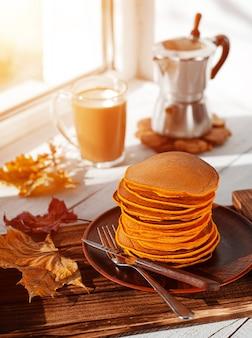 カボチャのパンケーキとウィンドウ上のコーヒーの朝食。